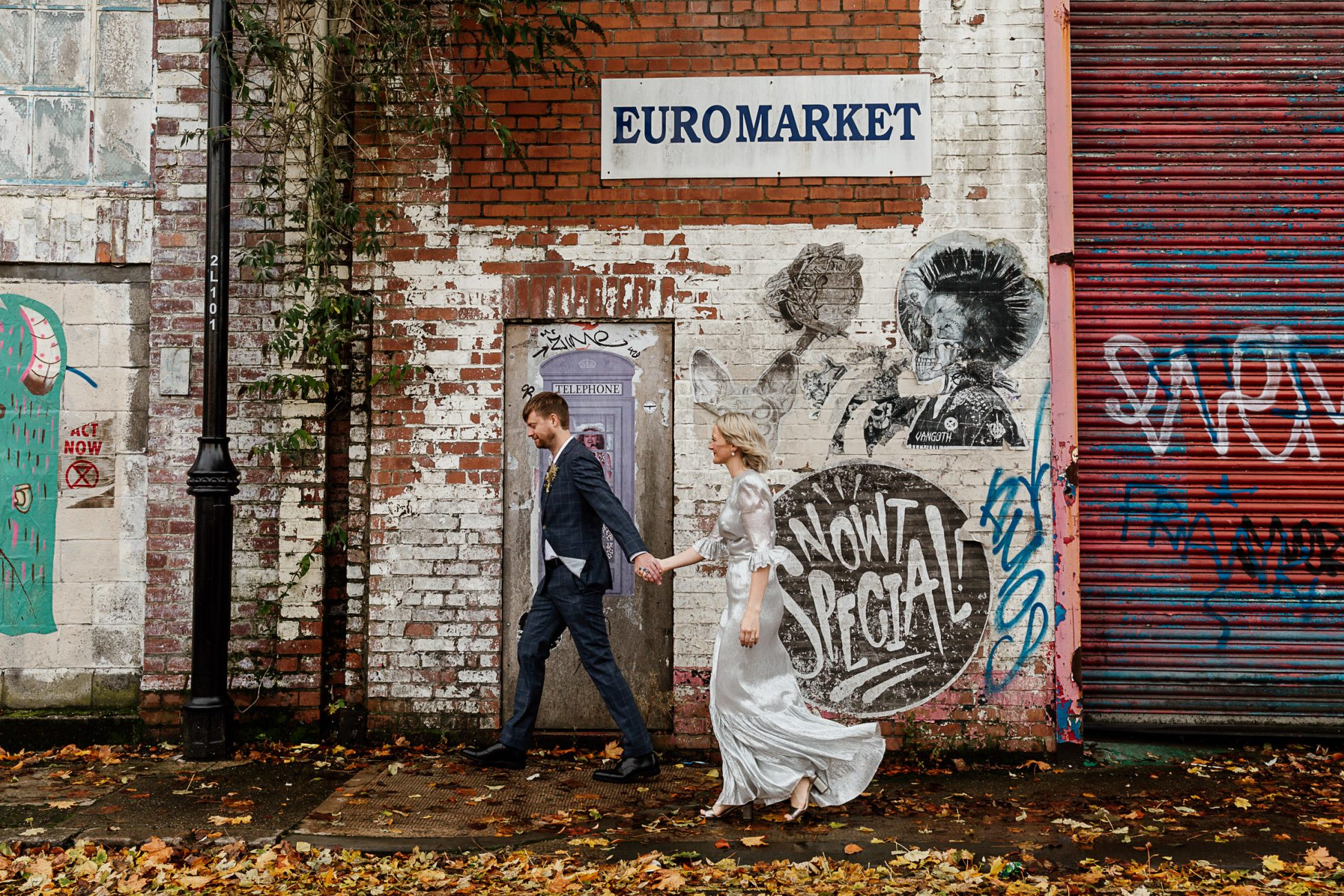 bride and groom walking past graffiti walls in the Ouseburn, Newcastle after their Biscuit Factory wedding