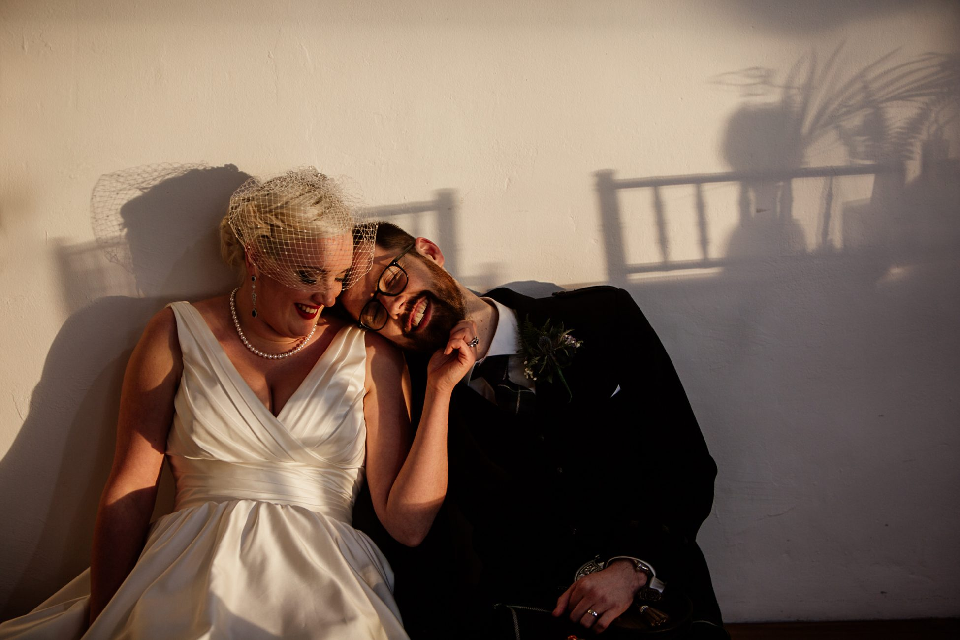 bride and groom sitting against a sunlit wall in Crear, Scotland