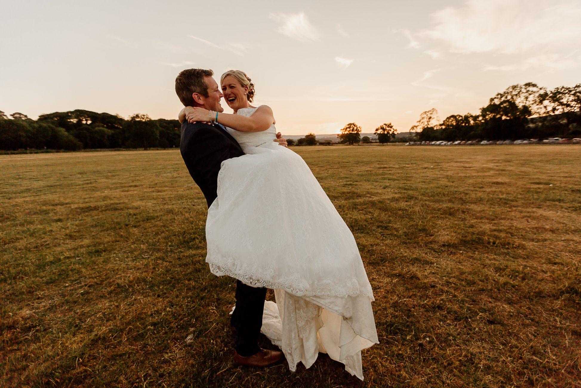 groom lifting up bride on a farm in Durham