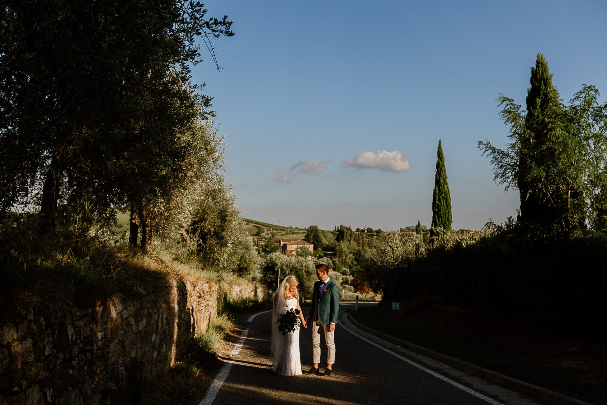 bride and groom standing in a shaft of sunlight on a country road in Tuscany, Italy