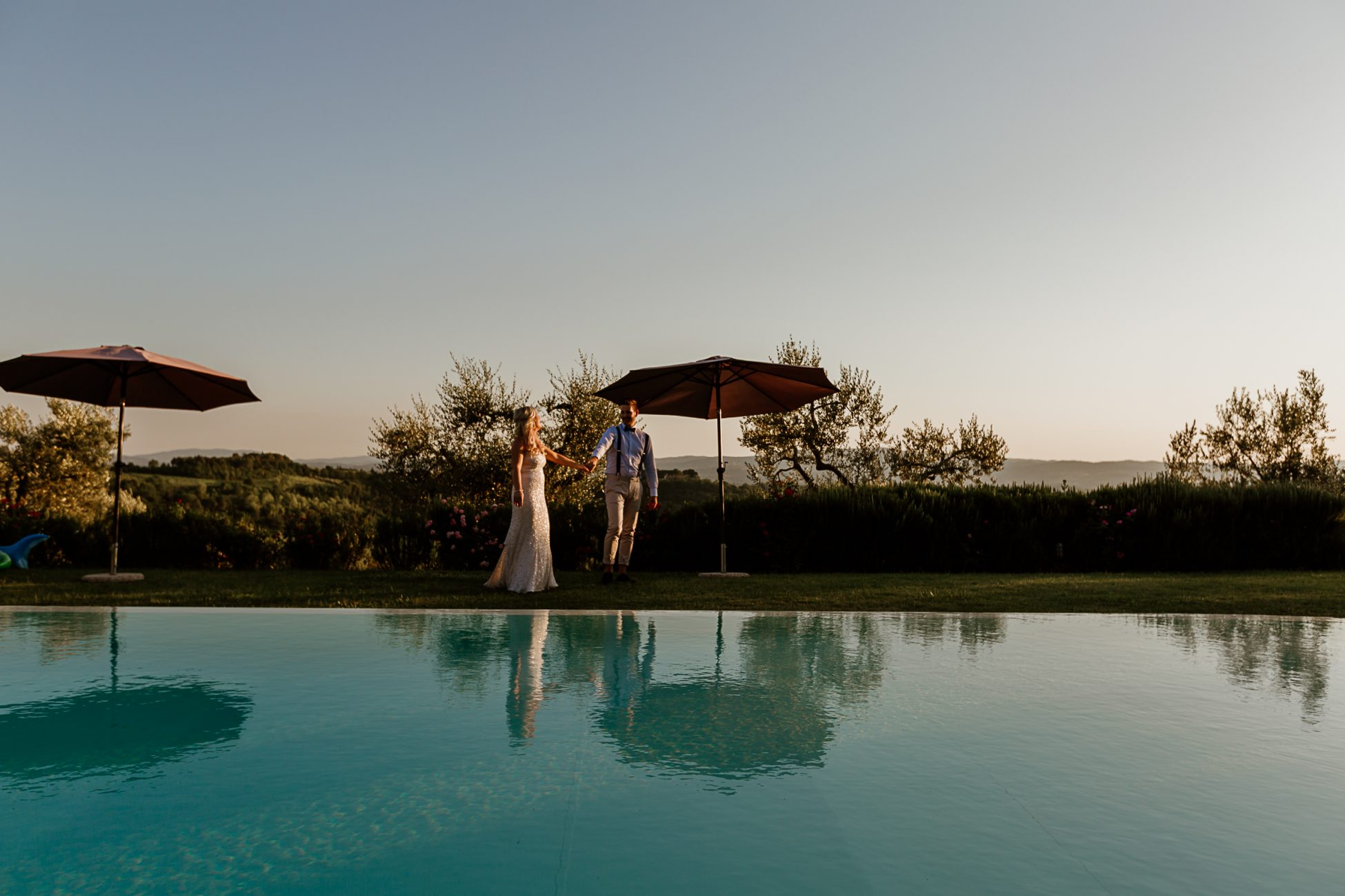 bride and groom dancing by a swimming pool