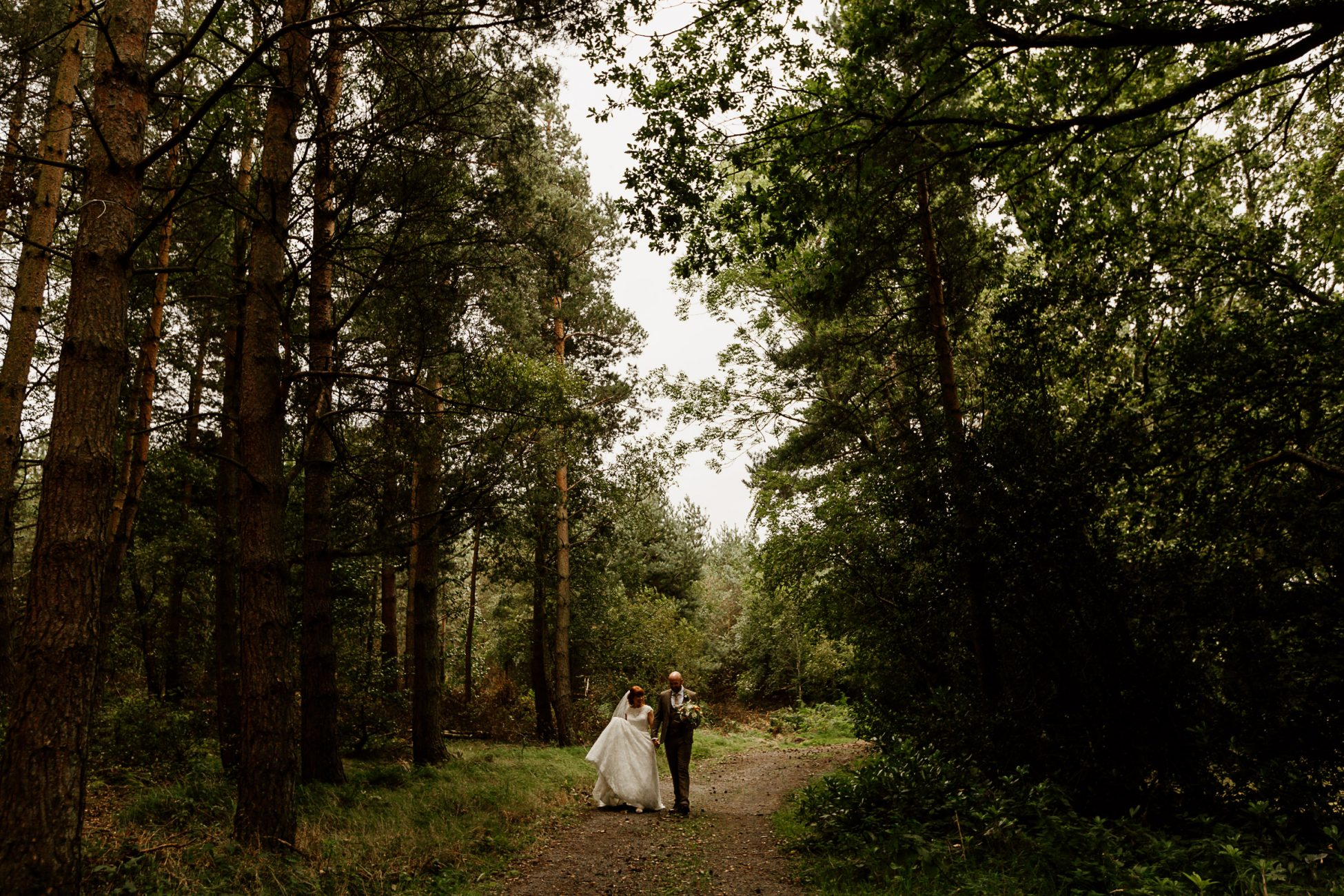 Bride and groom walking in the pine forest at Healey Barn, Northumberland