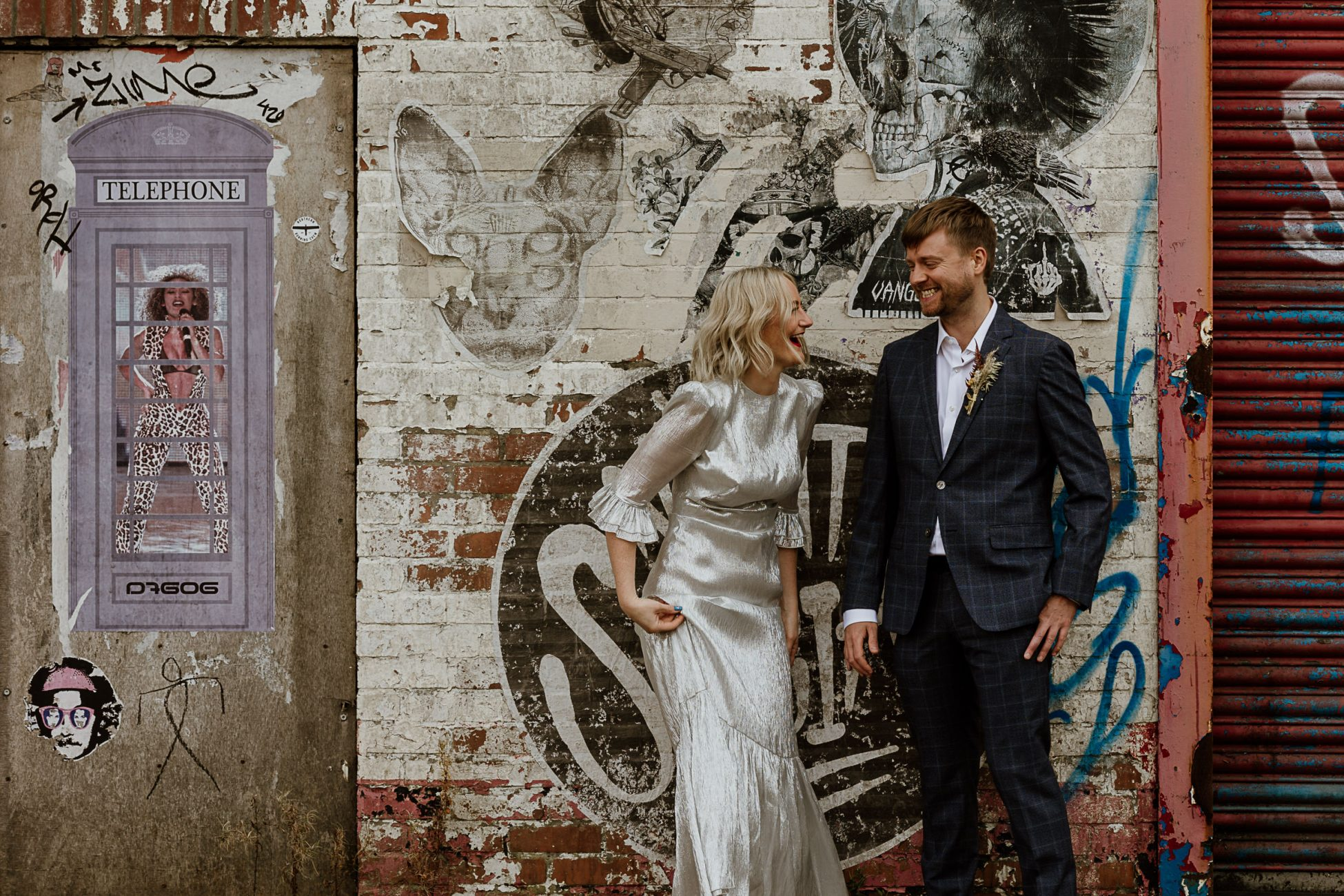 bride and groom laughing in front of a graffiti wall in the Ouseburn, Newcastle, Biscuit Factory wedding